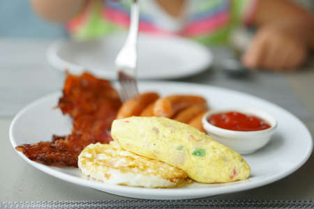 fried egg with omelet and grilled bacon on white dish for breakfast with hand of child or kid holding fork dipping sausage and ketchup or tomato sauce to morning food eating at home or restaurant