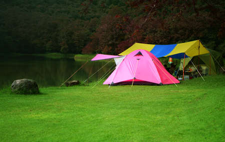 nature landscape pink camping tent under tree and colorful tarp on meadow and stone or rock with lake or river and camper jungle trekking for holiday relax on winter autumn and red leaves at ched khot