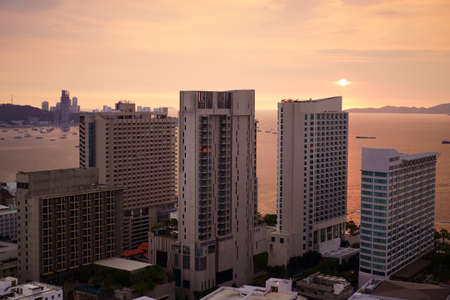 Pattaya city at chon buri in thailand on sunset or morning sunrise and warm sun light on orange sea water with boat and tower building or hotel by real estate business for holiday travel on golden sky