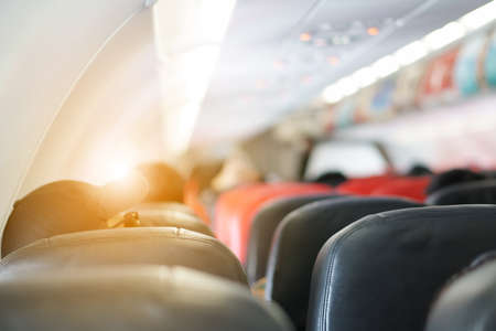 interior of airplane or aircraft with passengers or tourist and back people head on seats or chair in eco class and flying for holiday travel transportation and tourism to airport and window sunlight