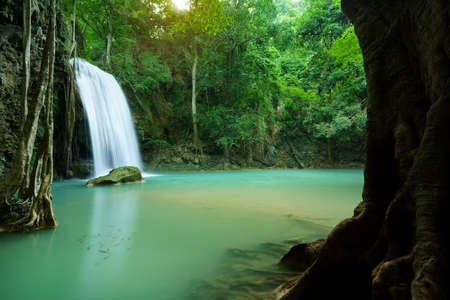 waterfall clear emerald water or blue pool with spa fish on summer season with rock and tree roots for holiday relax travel in green jungle or forest at erawan waterfall floor 3 for nature landscape Stockfoto
