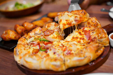 scooping hawaiian half deluxe pizza dough thick and soft to stretch cheese on tray with grilled chicken drumstick barbecue for lunch or breakfast and dinner to family eating food at italian restaurant
