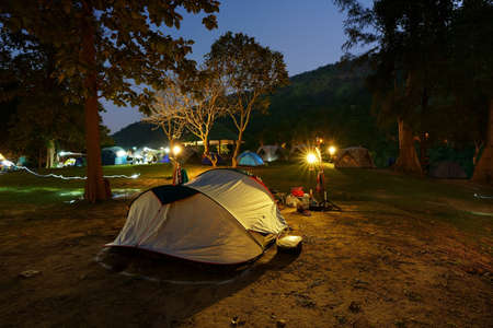 nature camping tent on grass and camp equipment in tree mountain forest at erawan national park on twilight night to warm white light on lantern yellow lamp for family vacation on holiday relax travel