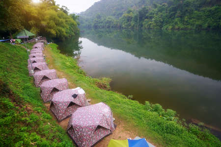 camping tent and cabin campsite on river khwae with water reflection and morning mist in green jungle at erawan waterfall national park for summer holiday relax and vacation travel trip on cool nature Stockfoto