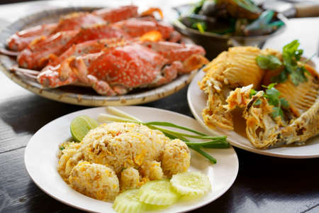 crab-shaped pork fried rice and steamed blue or horse crab with fried fish in dish and baked mussels on table for fresh seafood set to lunch and dinner with iodine and cholesterol food at restaurant