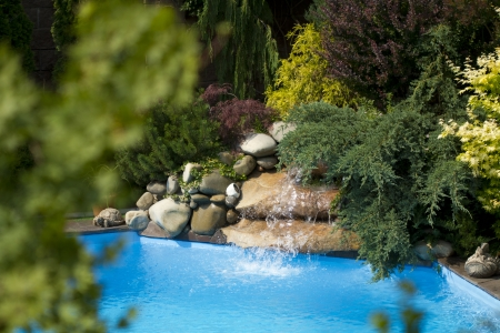 Swimming-pool water fall in home garden photo