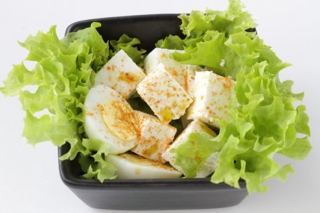 Cheese and hard boiled egg on a lettuce leaf photo