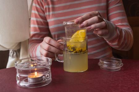 argousier: Boisson chaude à partir d'un argousier dans une tasse en verre