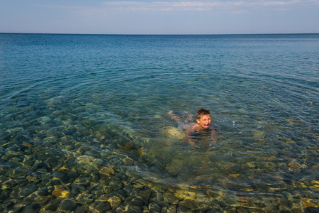 learns: The child learns to swim at the sea