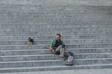 josep: BARCELONA, CATALONIA, SPAIN - OCTOBER 02, 2016.  The man with the dog on the stairs near the church of Temple Expiatori del Sagrat Cor (by Josep Miret) on Summit of Mount Tibidabo in Barcelona Stock Photo