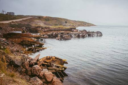 The old flooded wooden boats in water of the Barents Sea, Teriberka, Russia.