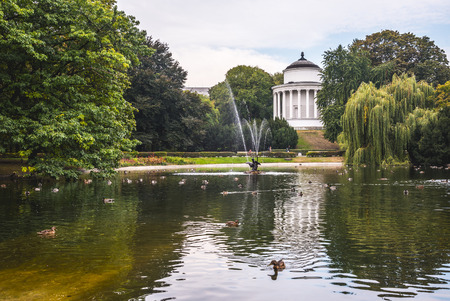 WARSAW, POLAND - SEPTEMBER 28, 2016: Water Tower, in the northwest part of the Saxon Garden (Warsaw, Poland), is situated by the ornamental lake surrounded by willows. Designed in 1852 by the architect Henryk Marconi