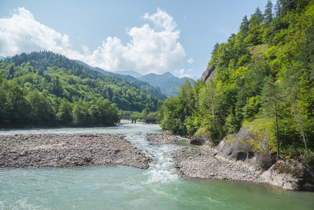 Summer landscape with river and mountain. Rocky shores of Belaya river. Caucasus mountains