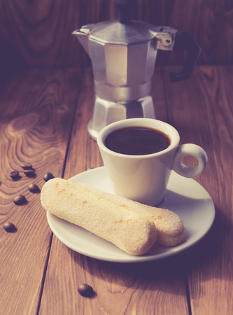 Cup of hot espresso, moka pot and cookies on the wooden table