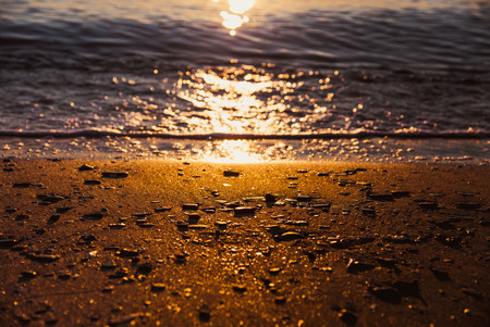 Beautiful gold sunset on Black Sea of Taman Gulf. Out of focus bokeh of blue water and gold sand with sun reflections  Stock Photo