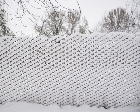 Rabitz fence covered with snow, selective focus Stock Photo