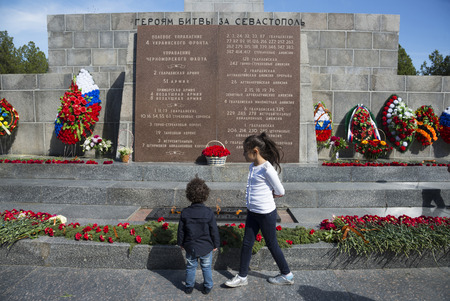 SEVASTOPOL / CRIMEA - MAY 10, 2017: Children near the Obelisk of Glory with eternal fire on the Sapun mount