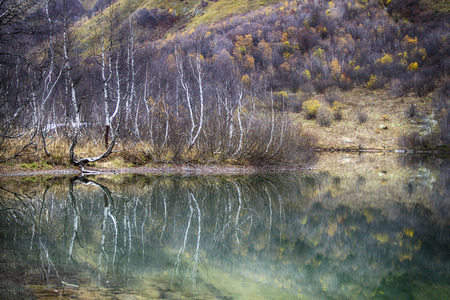 Kardyvach mountain lake with reflections. Autumn landscape in Caucasus mountains. Sochi, Russia