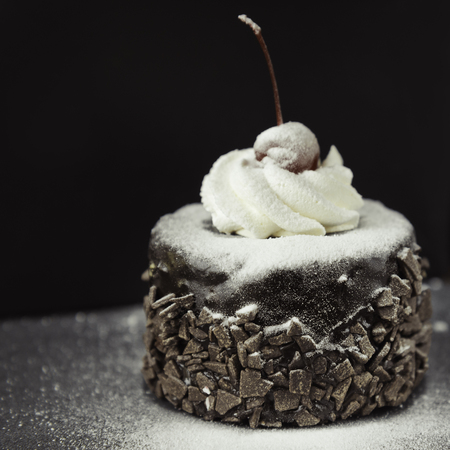 Delicious chocolate cake with red cherry on the black background