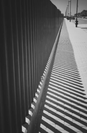 The shadow of the fence on the road