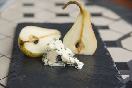 Blue cheese and ripe pears on the black plate Фото со стока
