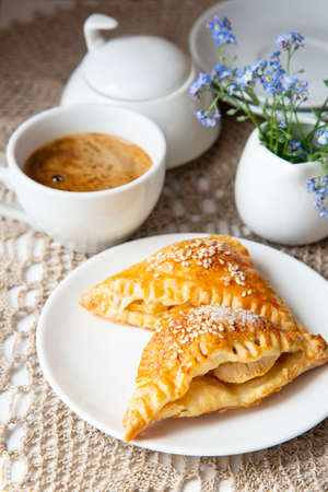 Apple samosa from puff pastry and cup of coffee