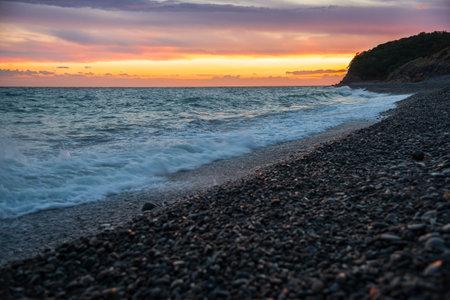 Bright yellow-orange sunset on the sea beach. Pebble beach on the Black Sea coast