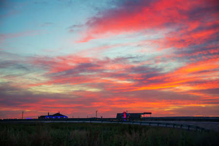 A roadside motel at a bend in the road. Scarlet sunset in the sky