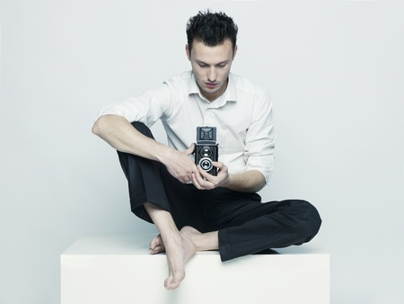 Stylish portrait of a young man with a camera photo