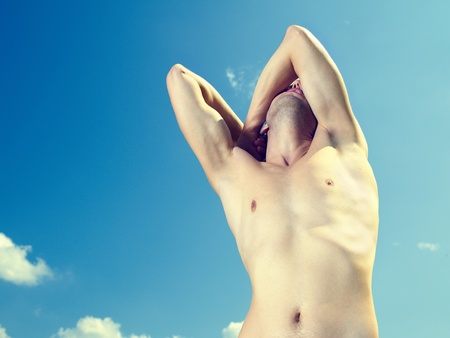 Naked young strong man against the blue sky photo