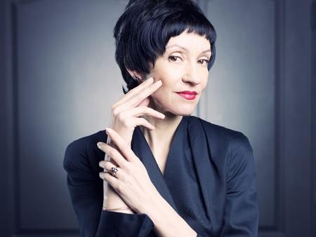 edad media: Retrato de una bella mujer de mediana edad contra el fondo negro
