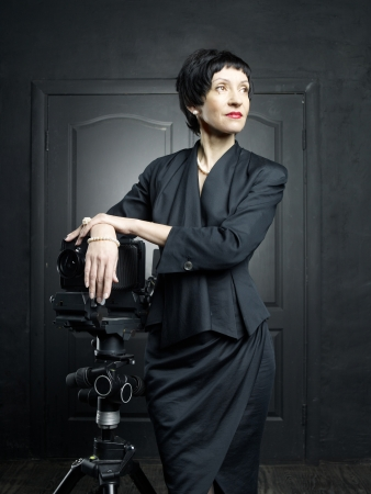 Portrait of a beautiful middle aged woman with a camera photo
