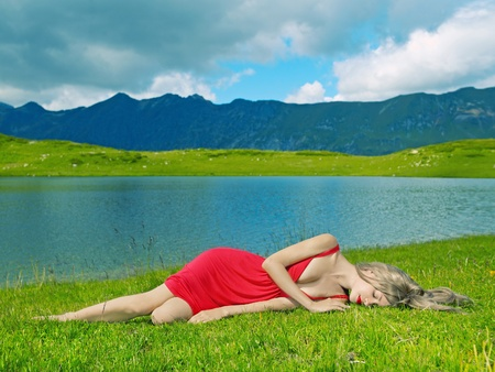 Elegant young lady in a red dress in a mountain lake