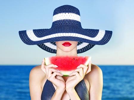 Junge stilvolle Dame mit Hut am Meer mit Wassermelone
