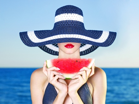 Young stylish lady in a hat at sea with watermelon Stock Photo - 10937463