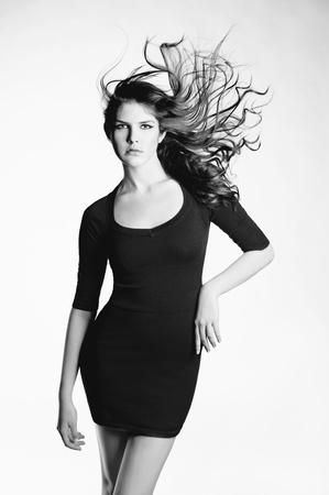 windblown: Photo of young beautiful woman in elegant black dress
