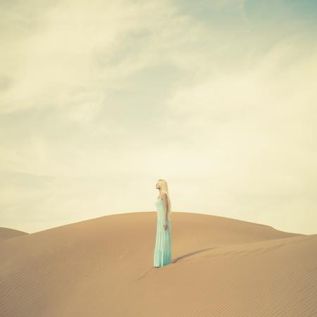 sexual pleasure: Beautiful blonde in a blue dress in an orange desert. UAE