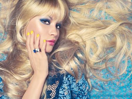 Beautiful sensual blonde lying on a blue pattern photo