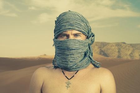 bedouin: Photo of brutal man in Bedouin scarf in desert