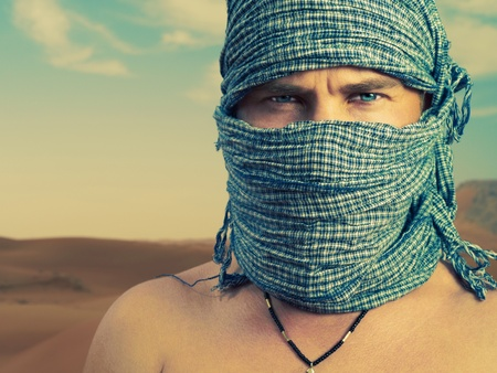 arabic desert: Photo of brutal man in Bedouin scarf in desert