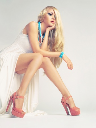 elegance fashion girls look sensuality young: Beautiful young woman sitting in a trendy shoes