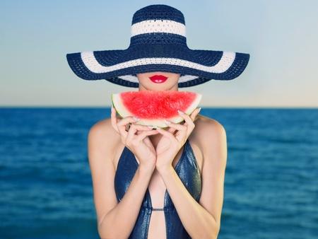 Jonge stijlvolle dame in een hoed op zee met watermeloen Stockfoto