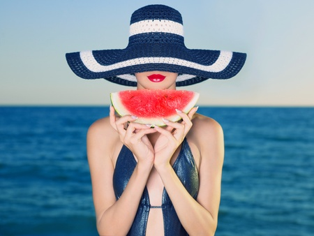 sexy food: Young stylish lady in a hat at sea with watermelon