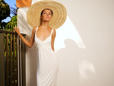 Portrait of a beautiful lady in a straw hat on the balcony Stock Photo - 12949683
