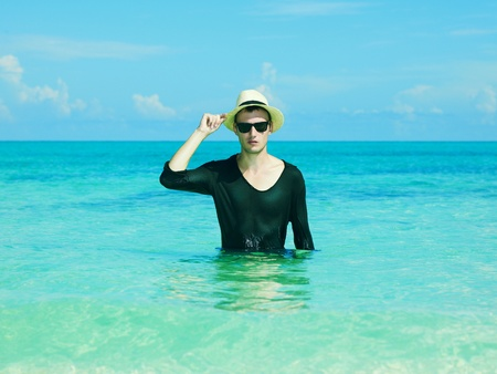 Young stylish man in the hat jumps on the sea Stock Photo - 12949672