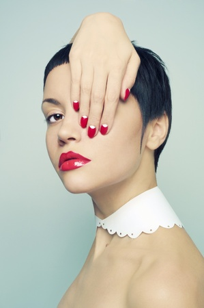 Fashion portrait of a beautiful young lady with bright nail polish photo