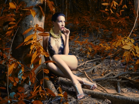 Glamorous lady in a lace leotard in a tropical forest
