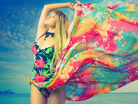 dream body: Luxurious blonde in color dress on the beach