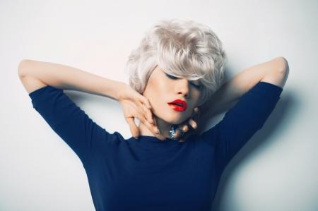 Mooie sexy blonde met rode lippenstift op de vloer liggen Stockfoto