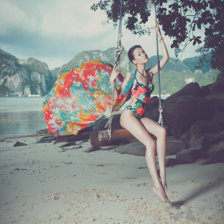 dress blowing in the wind: Bright young lady on the beach a swing